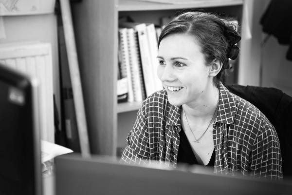 Female SLR employee smiling at her desk