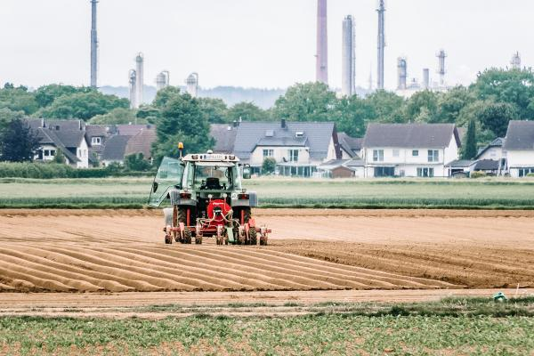 Tractor in field with near by industrial buildings