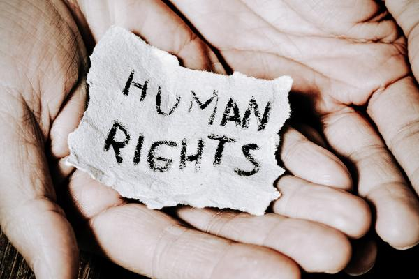 two hands holding a piece of paper with the words human rights