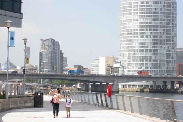 Photo of a woman and a boy walking at the water's edge in Belfast
