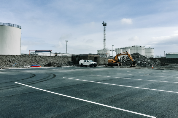 View across site car park towards waste facility, with digger in shot