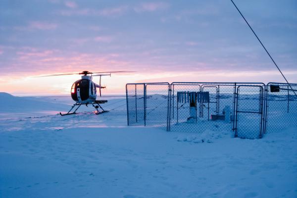 Helicopter landing in snowy Alaska before sunrise
