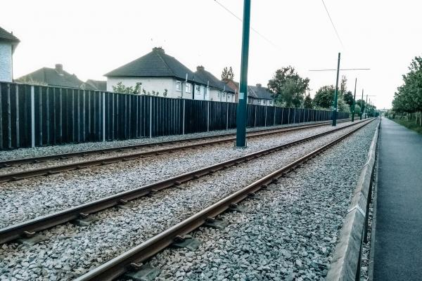 railway line with noise barrier between it and houses beyond