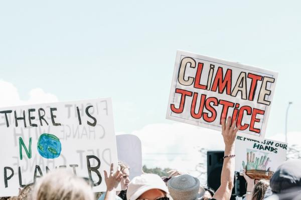 protestors holding signs saying 'climate justice'