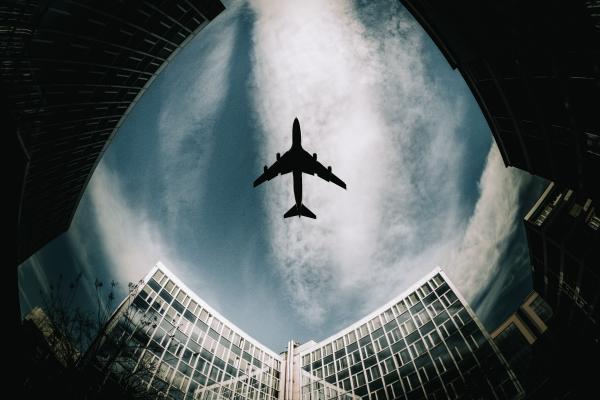view of aeroplane overhead from between buildings