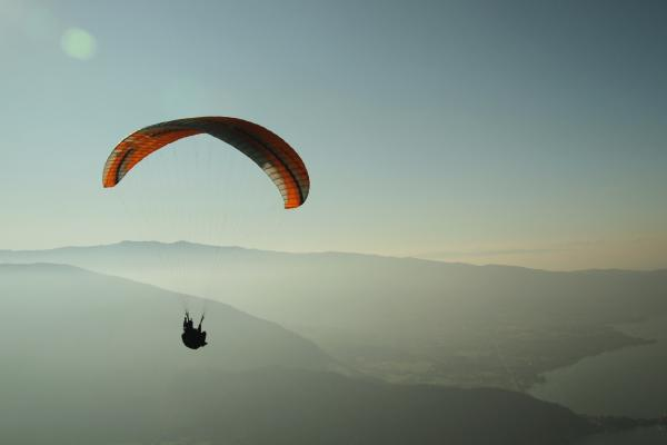person above the hills with a parachute