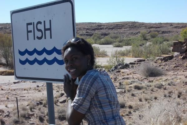 Ester posing with a sign reading 'fish'