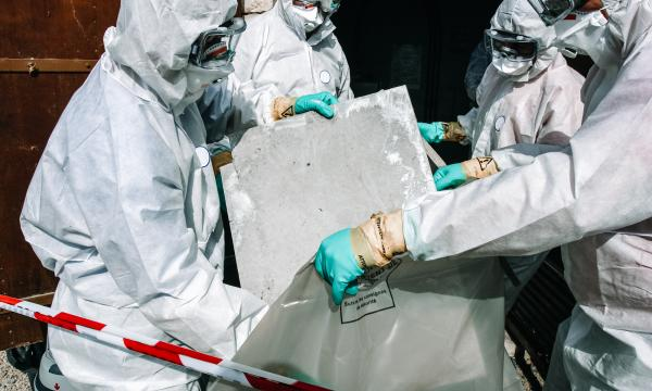 four people in PPE for hazardous materials